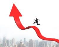 Hombre de negocios que corre en la flecha para arriba que dobla la línea de tendencia con el cityscap Fotografía de archivo