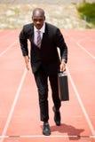 Hombre de negocios que corre en una pista corriente Imagenes de archivo
