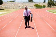 Hombre de negocios que corre en una pista corriente Imagen de archivo libre de regalías