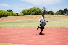 Hombre de negocios que corre en una pista corriente Foto de archivo libre de regalías