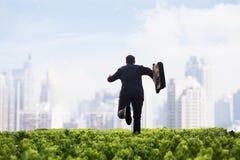 Hombre de negocios que corre hacia la ciudad con una cartera en un campo verde con las plantas Imagen de archivo