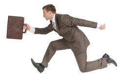 Hombre de negocios que corre rápidamente con la maleta Imágenes de archivo libres de regalías