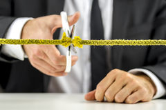 Hombre de negocios que corta la cuerda amarilla Fotografía de archivo