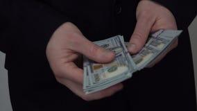 Hombre de negocios que cuenta U S 100 cuentas de dólar almacen de video