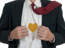 Hombre de negocios que cuida con el corazón del oro fotografía de archivo