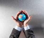 Hombre de negocios que cuida que protege el futuro del planeta para la salud del ambiente imágenes de archivo libres de regalías