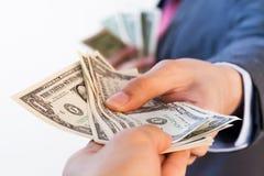 Hombre de negocios que da billetes de banco a otra persona Corrupción y Fotografía de archivo libre de regalías