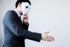 Hombre de negocios que da el apretón de manos deshonesto que oculta en la máscara - autobús imagen de archivo libre de regalías