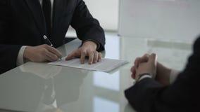 Hombre de negocios que da el contrato masculino de la cooperación del colega para firmar, sociedad almacen de metraje de vídeo