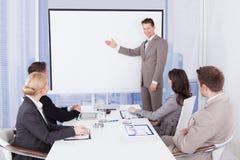 Hombre de negocios que da la presentación a los colegas en oficina Foto de archivo