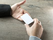 Hombre de negocios que da la tarjeta de visita al socio comercial con el fondo de madera de la tabla Fotografía de archivo libre de regalías