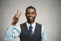 Hombre de negocios que da la victoria, muestra de dos fingeres Imagenes de archivo
