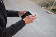 Hombre de negocios que descansa de trabajo y mientras que envía de mensajes y habla con su tableta blanca Imagen de archivo libre de regalías