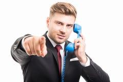 Hombre de negocios que detiene al receptor de teléfono azul que señala la cámara Imágenes de archivo libres de regalías