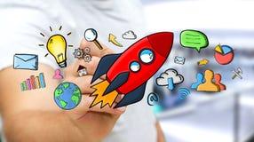Hombre de negocios que dibuja iconos rojos del cohete y de las multimedias con una pluma Fotos de archivo