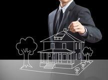 Hombre de negocios que dibuja la casa ideal Foto de archivo libre de regalías