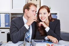Hombre de negocios que dice a mujer un secreto Imágenes de archivo libres de regalías
