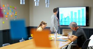 Hombre de negocios que discute con los colegas sobre la pantalla del lcd en la sala de conferencias 4k almacen de video