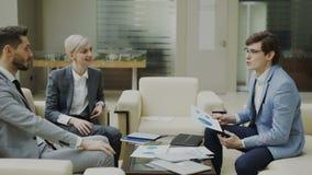 Hombre de negocios que discute informes financieros con los socios comerciales femeninos y masculinos que se sientan en el sofá e