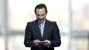Hombre de negocios que disfruta del juego online almacen de video