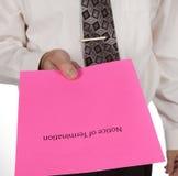 Hombre de negocios que distribuye un aviso de la terminación o de la hoja rosa Fotografía de archivo