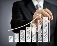 Hombre de negocios que drena un gráfico cada vez mayor Imagen de archivo libre de regalías