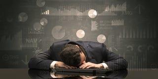 Hombre de negocios que duerme con las cartas, los gráficos y concepto de los informes imagenes de archivo