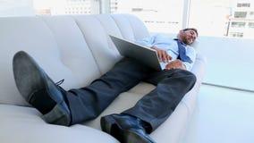 Hombre de negocios que duerme en el sofá con su ordenador portátil almacen de video