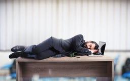 Hombre de negocios que duerme sobre un escritorio debido trabajar demasiado Fotos de archivo libres de regalías
