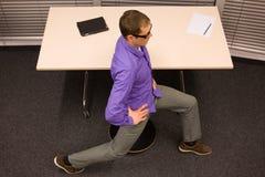 hombre de negocios que ejercita en el escritorio en el lugar de trabajo Imagen de archivo
