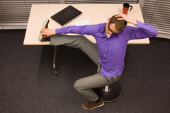 hombre de negocios que ejercita en el escritorio en el lugar de trabajo Fotografía de archivo libre de regalías