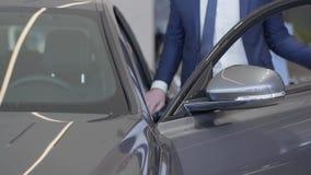 Hombre de negocios que elige el coche en la representación moderna El hombre alto abre la puerta y se incorpora en automóvil en c metrajes