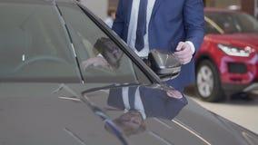Hombre de negocios que elige el coche en la representación moderna Hombre irreconocible en el traje que toca el espejo del automó almacen de video