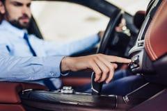 Hombre de negocios que empuja el botón en el tablero de instrumentos en el coche fotografía de archivo libre de regalías
