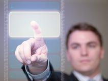 Hombre de negocios que empuja el botón que brilla intensamente en la pantalla translúcida. Fotografía de archivo libre de regalías