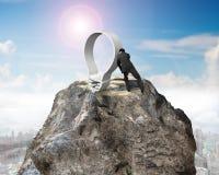 Hombre de negocios que empuja la bombilla en pico de montaña euro del esquema de la muestra Imagen de archivo libre de regalías