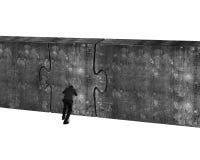 Hombre de negocios que empuja la puerta enorme del rompecabezas del muro de cemento Fotografía de archivo libre de regalías