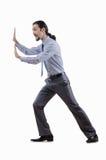 Hombre de negocios que empuja obstáculos virtuales Foto de archivo libre de regalías