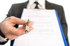 Hombre de negocios que entrega un contrato para la firma Imágenes de archivo libres de regalías