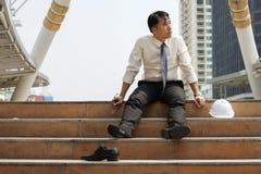 Hombre de negocios que es el sentarse cansado o subrayado solamente en las escaleras Foto de archivo libre de regalías