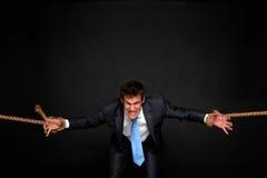 Hombre de negocios que es tirado por la cuerda en ambas caras. Imagen de archivo libre de regalías