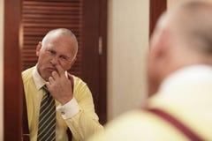 Hombre de negocios que escoge su nariz Imagen de archivo libre de regalías