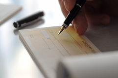 Hombre de negocios que escribe la verificación Fotografía de archivo libre de regalías