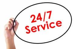Hombre de negocios que escribe 24/7 palabra de servicio con la pluma Imagen de archivo libre de regalías