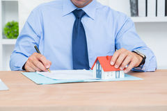 Hombre de negocios que escribe un contrat antes de firmarlo Fotos de archivo