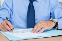 Hombre de negocios que escribe un contrat antes de firmarlo Foto de archivo