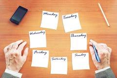 Hombre de negocios que escribe un plan a la semana Foto de archivo libre de regalías
