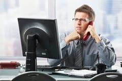 Hombre de negocios que escucha la llamada de la línea horizonte en oficina foto de archivo