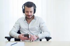 Hombre de negocios que escucha la música con los auriculares imagenes de archivo