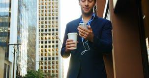 Hombre de negocios que escucha la música y que usa el teléfono móvil almacen de metraje de vídeo